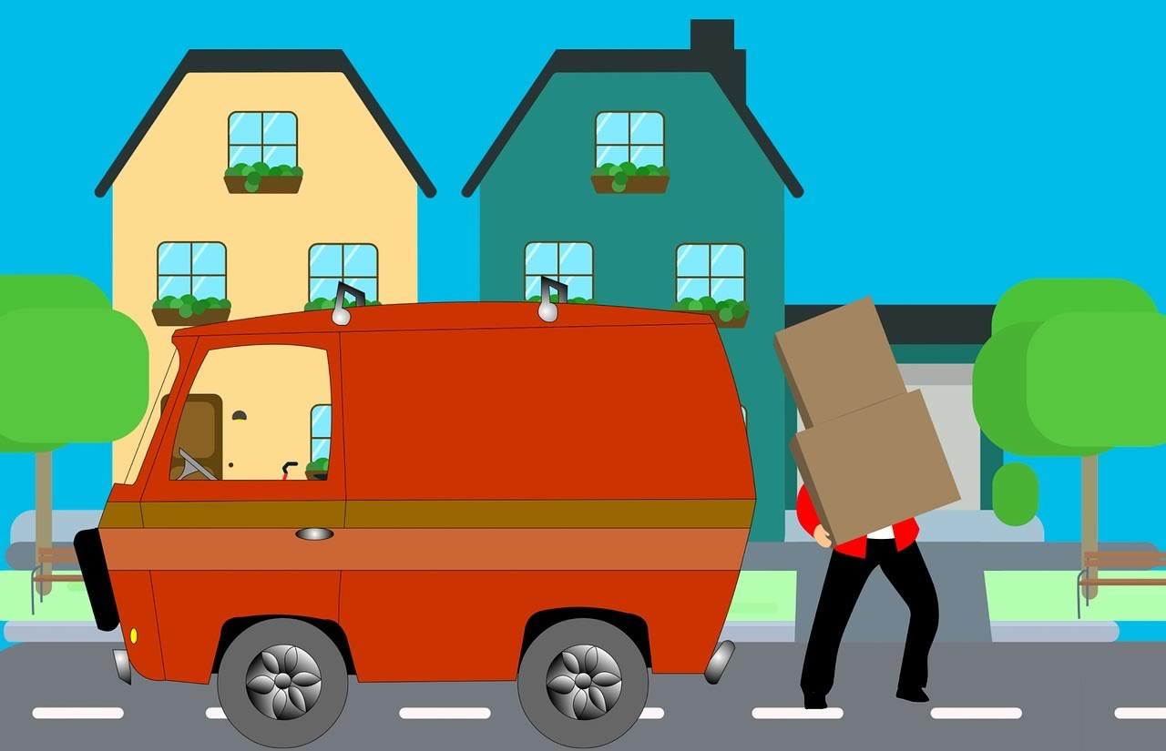 déménageur avec cartons devant un camion rouge